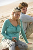 Young pregnant couple sitting on mat at beach royalty free stock photo