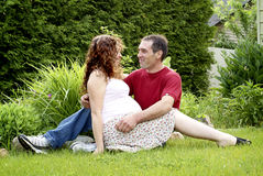 Young Pregnant Couple Sitting Together. A young, happy, pregnant couple in love sitting on grass outside enoying each other's company stock images