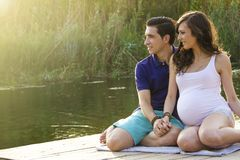 Young pregnant couple sitting on a wood platform stock photos