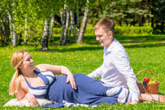Young pregnant couple on a sunny day, relax. On the lawn Stock Photo