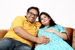 Young pregnant couple is touching belly with sitting on the couch royalty free stock images