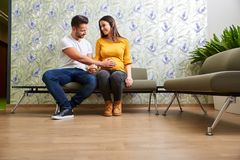 Young pregnant couple waiting. A beautiful young pregnant couple sitting in the doctors waiting room Royalty Free Stock Photo