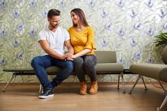 Young pregnant couple waiting. A beautiful young pregnant couple sitting in the doctors waiting room Stock Photo