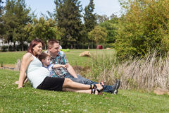 Young pregnant family relaxing in the park Stock Image