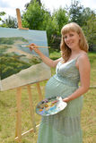 The young pregnant female artist draws a picture oil paints. In the open air royalty free stock photography