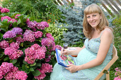 The young pregnant female artist draws water color paints a blossoming hydrangea Stock Photos