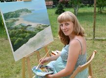 The young pregnant female artist paints a picture, sitting at an easel.  stock images