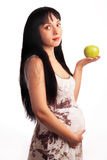 Young pregnant girl is eating an apple. Beautiful, young pregnant girl is eating an apple. Mom, Mother, Motherhood, waiting for the child birth Royalty Free Stock Photography