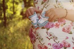 Young pregnant girl. Hands of a pregnant girl holding a close-up of baby booties in the parkr. Young pregnant girl. Hands of a pregnant girl holding a close-up stock images