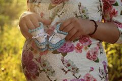 Young pregnant girl. Hands of a pregnant girl holding a close-up of baby booties in the parkr. Young pregnant girl. Hands of a pregnant girl holding a close-up stock photos