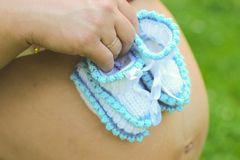 Young pregnant girl. Hands of a pregnant girl holding a close-up of baby booties in the park.  stock images
