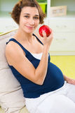Young pregnant girl holding red apple Stock Image