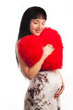 Young pregnant girl hugging a soft big heart Stock Image