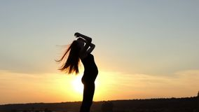 Young pregnant girl shake her hairs in slow motion at sunset. stock footage