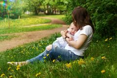 Family. Mom and son in park. Young pregnant girl sits on lawn in city park. Mother hugs her son. Little boy is happy. Blur effect Stock Image