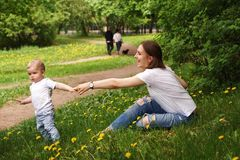 Family. Mom and son in park. Young pregnant girl sits on lawn in city park. Son holds his mother`s hand. He calls her to go walking with him Stock Images