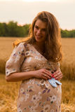 A young pregnant girl among wheat fields. Girl in a gentle way expectant mother. Beautiful country landscape. Photos for magazines, posters and websites Stock Images