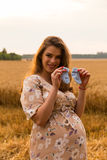 A young pregnant girl among wheat fields. Girl in a gentle way expectant mother. Beautiful country landscape. Photos for magazines, posters and websites Royalty Free Stock Photo