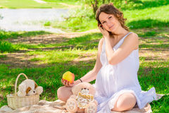 Young pregnant girl in a white sarafan on a plaid in a park Royalty Free Stock Photo