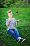 Young pregnant juggles with apples Stock Image