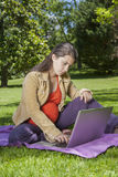 Young pregnant with laptop Stock Images