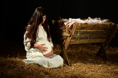 Young Pregnant Mary with Manger. Pregnant Mary holding stomach at manger on Christmas Eve Stock Photo