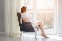 Young pregnant mom sitting on the armchair. Near window. Dressed in white dress. Happy young mother awaiting baby, love and happiness, new life concept Stock Photo