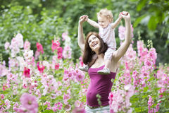 Young pregnant mother with baby daughter in flowers Royalty Free Stock Photo