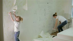 A young pregnant mother and a daughter pulling off wallpaper. stock video