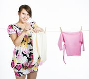 Young pregnant mother hangs out to dry a kidswear stock images