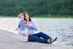Young pregnant mother and her baby daughter on shore of river Royalty Free Stock Image
