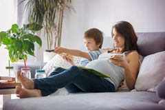 Young pregnant mother and her boy, eating tasty pizza at home, w Stock Photography