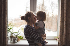 Young pregnant mother and son playing, hugging, kissing the wind. Young pregnant mother with dreadlocks and her son playing, hugging, kissing the window real royalty free stock photography