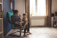 Young pregnant mother and son read book and play hide and seek l Stock Image