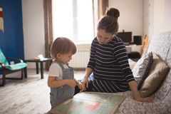 Young pregnant mother and son reading a book, lifestyle, Royalty Free Stock Photo