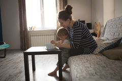 Young pregnant mother and son reading a book, lifestyle, Stock Photos