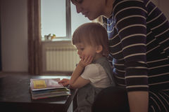 Young pregnant mother and son reading a book, lifestyle, Royalty Free Stock Images