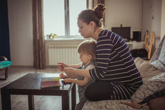 Young pregnant mother and son reading a book, lifestyle, Royalty Free Stock Photography