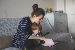 Young pregnant mother and son reading a book, lifestyle, Stock Photo