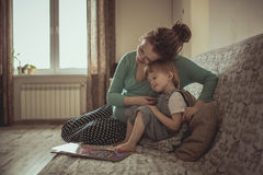 Young pregnant mother and son reading a book on sofa, lifestyle, Royalty Free Stock Photo