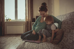 Young pregnant mother and son reading a book on sofa, lifestyle, Stock Image