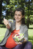 Young pregnant offering salad Stock Photos