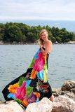 Young pregnant smiling woman in pareo. Young pregnant smiling woman dressed in colored pareo is looking forward near sea royalty free stock image