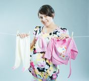 Young pregnant mother hangs out to dry a kidswear stock photography