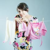 Young pregnant mother hangs out to dry a kidswear royalty free stock photos