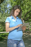 Young pregnant touching tablet serious Royalty Free Stock Photos