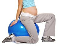 Young pregnant woman. Making exercise on a fitness ball Stock Image