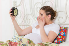 Young pregnant woman with alarm clock. Stock Photos
