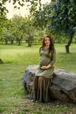Young pregnant woman in anticipation of a baby sitting on a big stone in a park in the sun rays Stock Photography