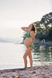 Young pregnant woman on the beach on sunrise stock photography